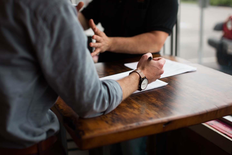 Egy ügyfél ecseteli elképzeléseit egy kollégának, aki figyelmesen lejegyzi a hallottakat, hogy előkészítse a munkát. A közeli életképen az asztal, papírok, és a férfiak kezei látszanak.
