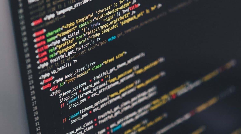 Az LCD monitorról készült közelképen színes HTML kódsor látható.