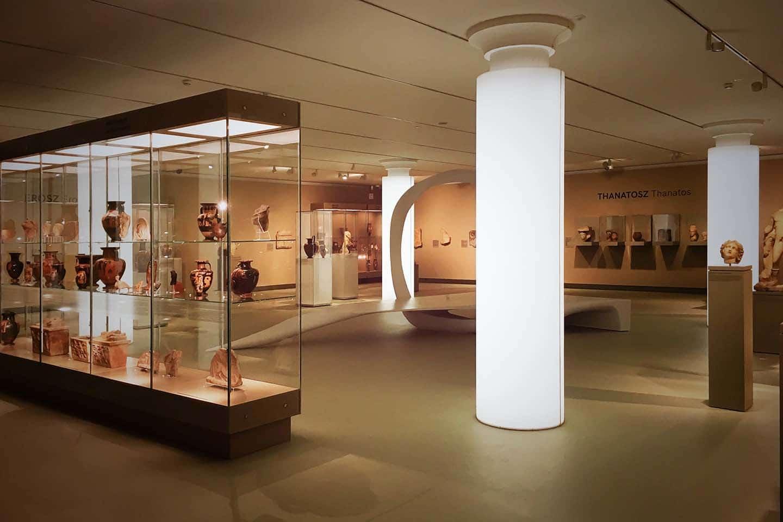 A Szépművészeti Múzeum ókor kiállítása. Antik vázák és edények, valamint más műtárgyak sorakoznak egy impozáns üvegvitrinben az előtérben, még kicsivel hátrébb, fehér, világító oszlopok egy organikus installáció, más vitrinek és szobrok látszanak.
