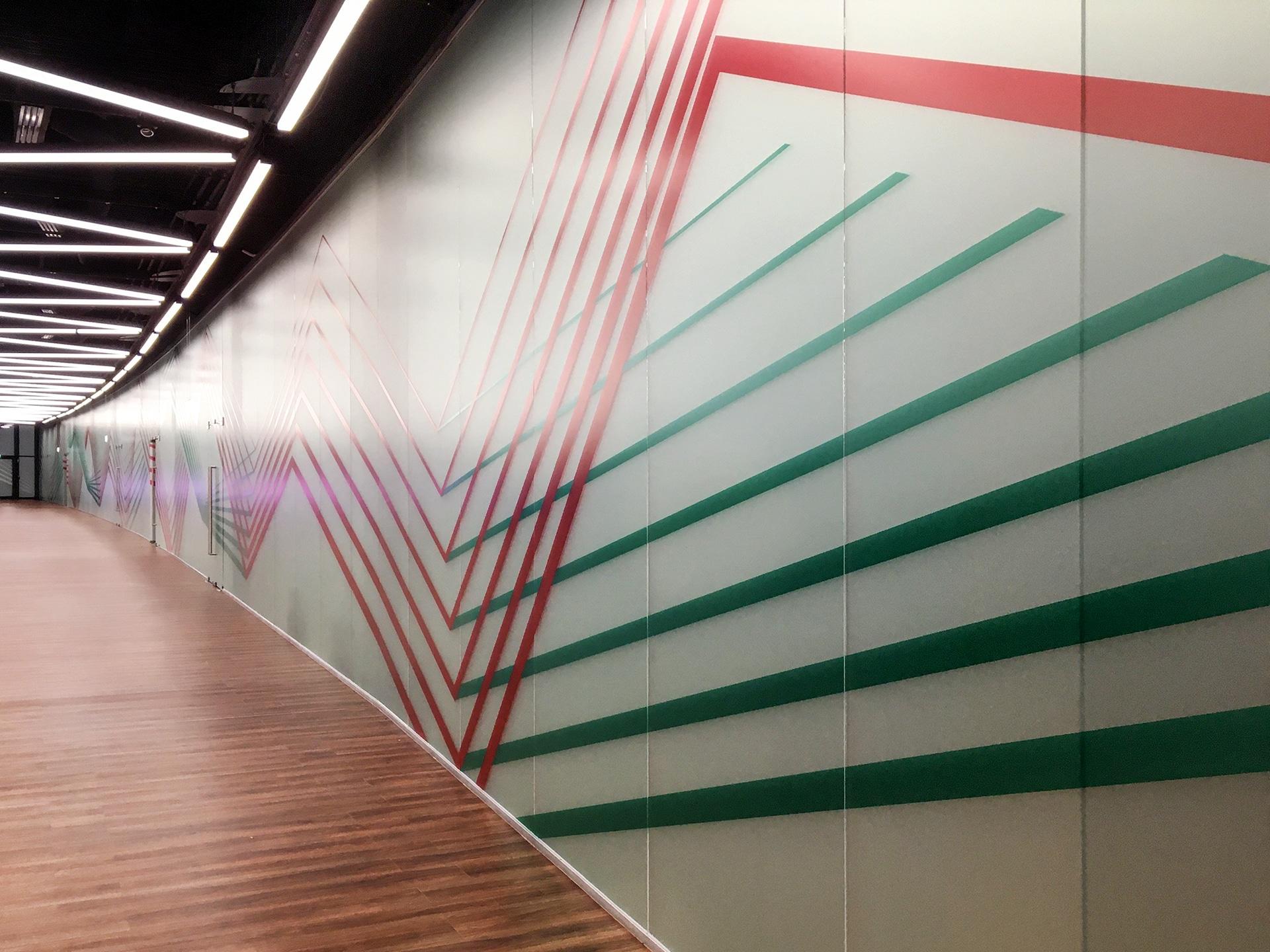 Több tíz méter hosszan futó fehér plexi elválasztófal a Puskás Arénában, amin vörös és zöld absztrakt díszítősávok futnak végig.