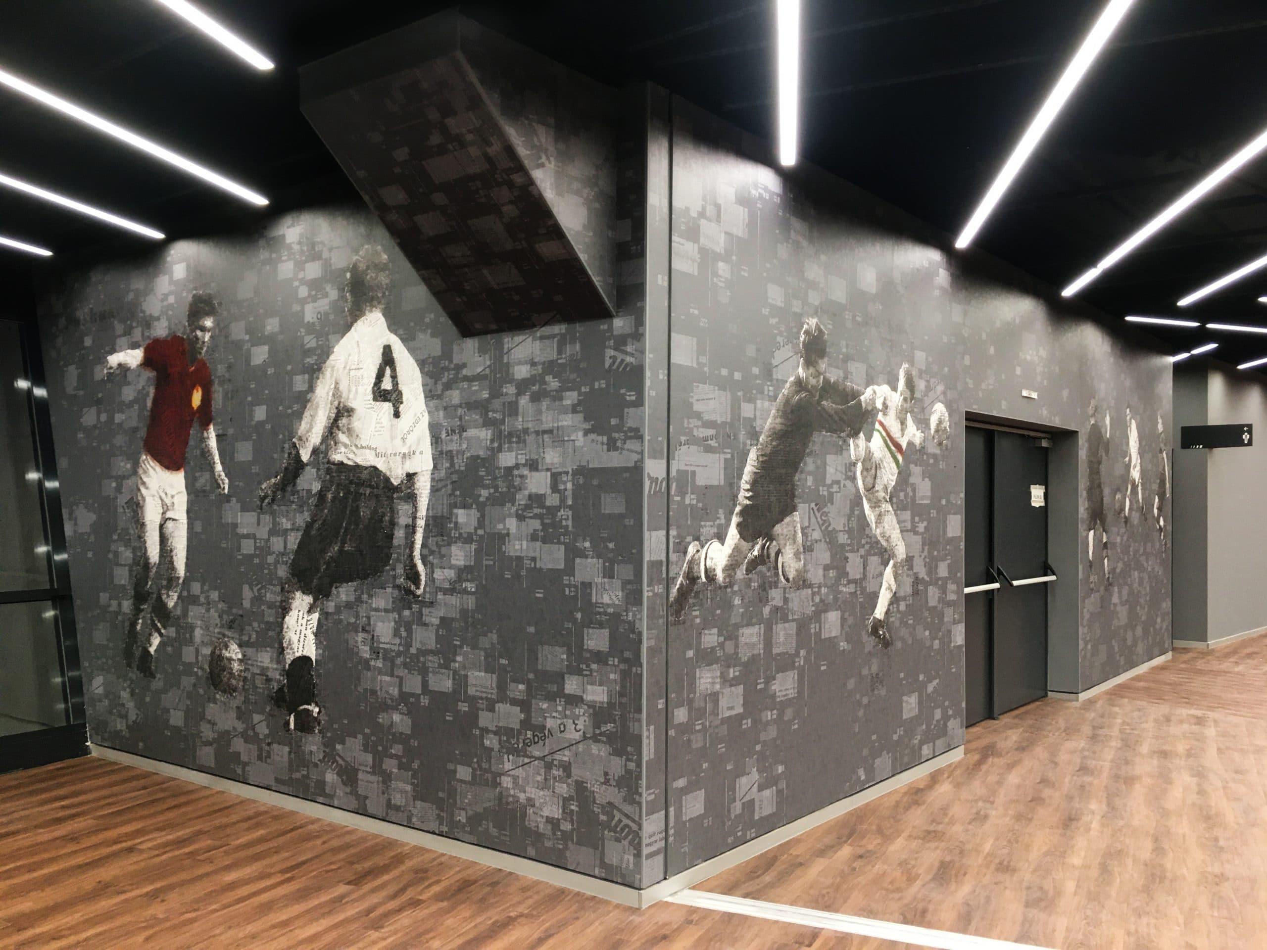 Fekete, fehér, szürke és vörös színekkel nyomtatott egész falat betöltő tapéta, ami focistákat ábrázol játék közben egy újságcikkekből összeállított kollázs formájában.