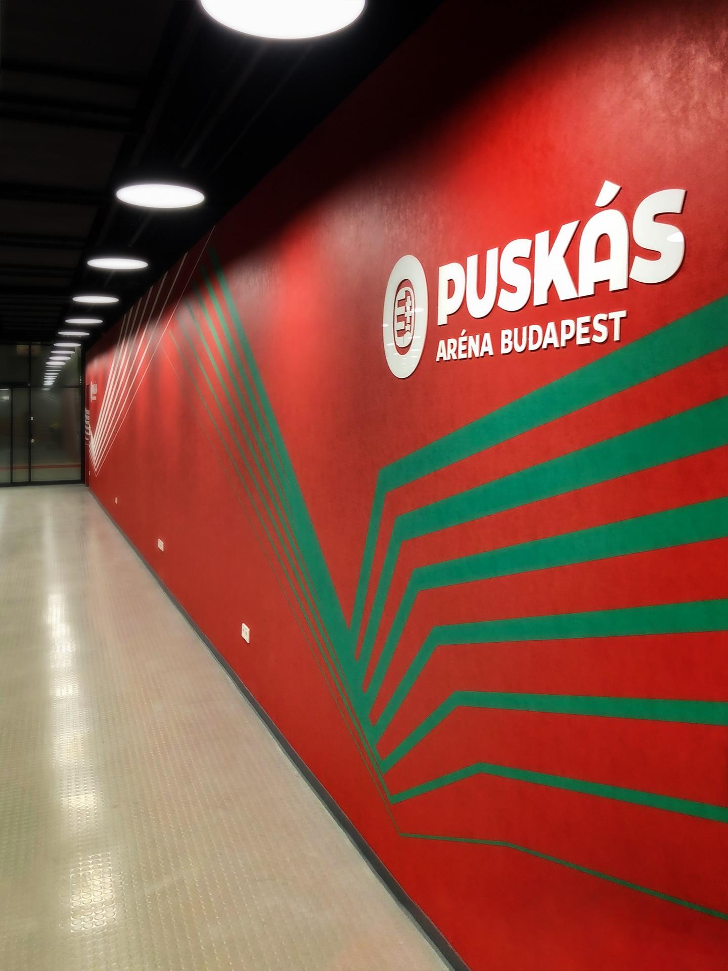 Vörös falfelületen zöld és fehér sávok futnak, fölöttük a Puskás Aréna nagyméretű fehér plexilogójával.