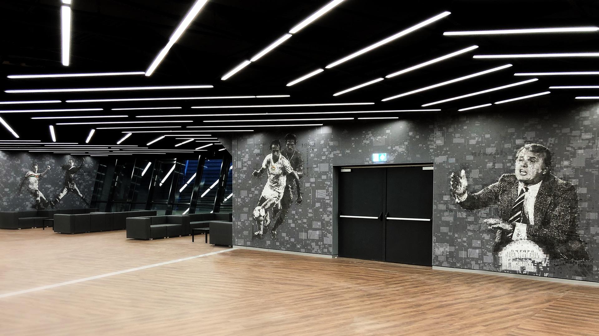 Nagylátószögű kép a VIP páholyról. A falakon az egyedi szürke nyomatott tapétával, amin mozaikszerű foci életképek látszanak.