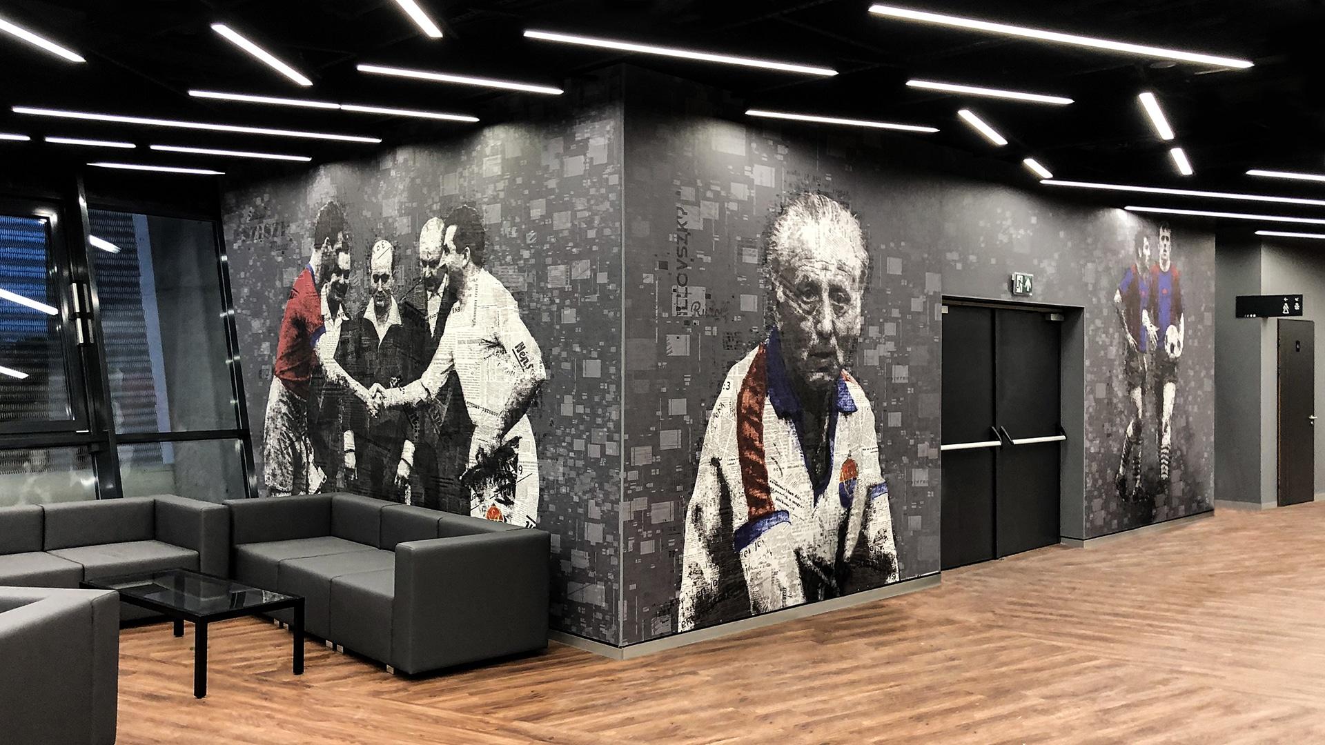 Egy kép a VIP páholyból kényelmes szürke ülőgarnitúrával, prémium fekete-üveg dohányzóasztallal és látványos, nyomtatott tapétával a falakon. A fekete, fehér, szürke, vörös és kék színekkel nyomtatott egész falat betöltő tapéta jeleneteket és portrékat ábrázol a magyar foci történetéből egy újságcikkekből összeállított kollázs formájában.