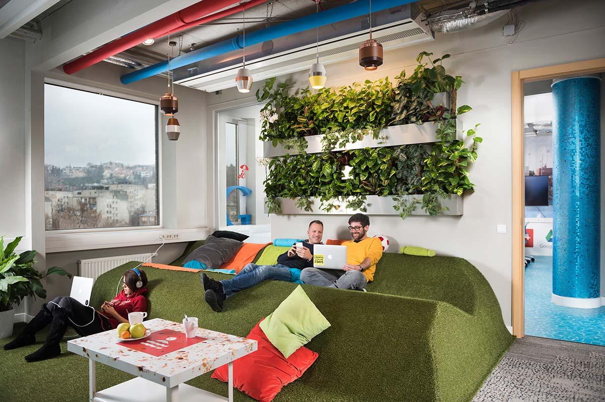 A Google Budapest iroda közösségi tere zöld, füvet imitáló pihenővel, stílusos világítással és növényekkel a falon. Néhány alkalmazott beszélget és relaxál színes párnák között.
