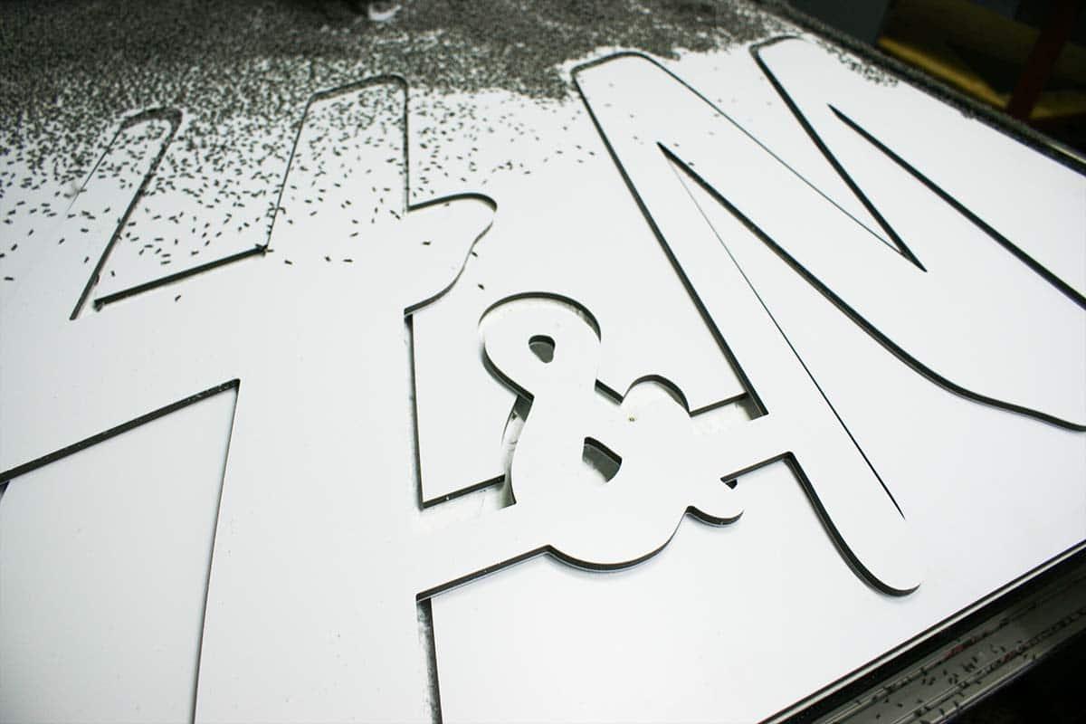 A CNC gép épp most marta ki a nagyméretű H&M logót egy fehér lemezből. A táblán még rajta vannak a forgácsok is.