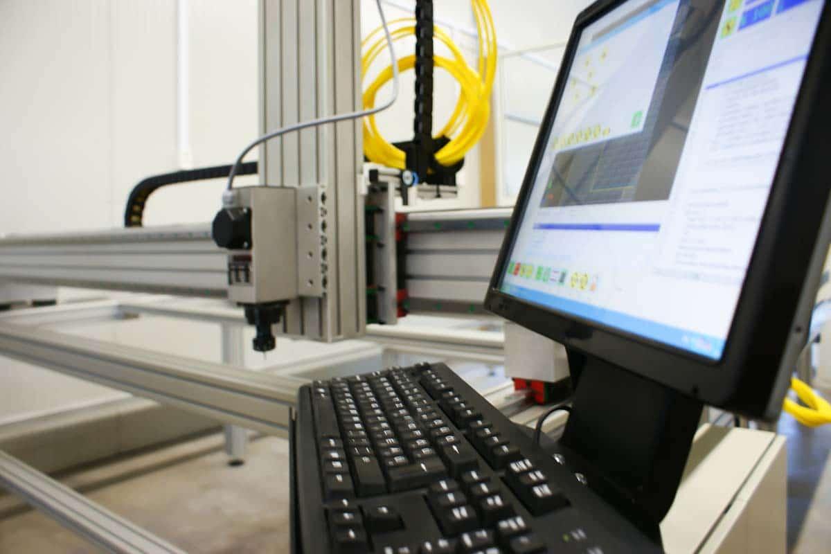 A kép előterében a monitoron a gép vezérlőszoftvere látszik, a háttérben pedig maga a CNC gép készül az indulásra.