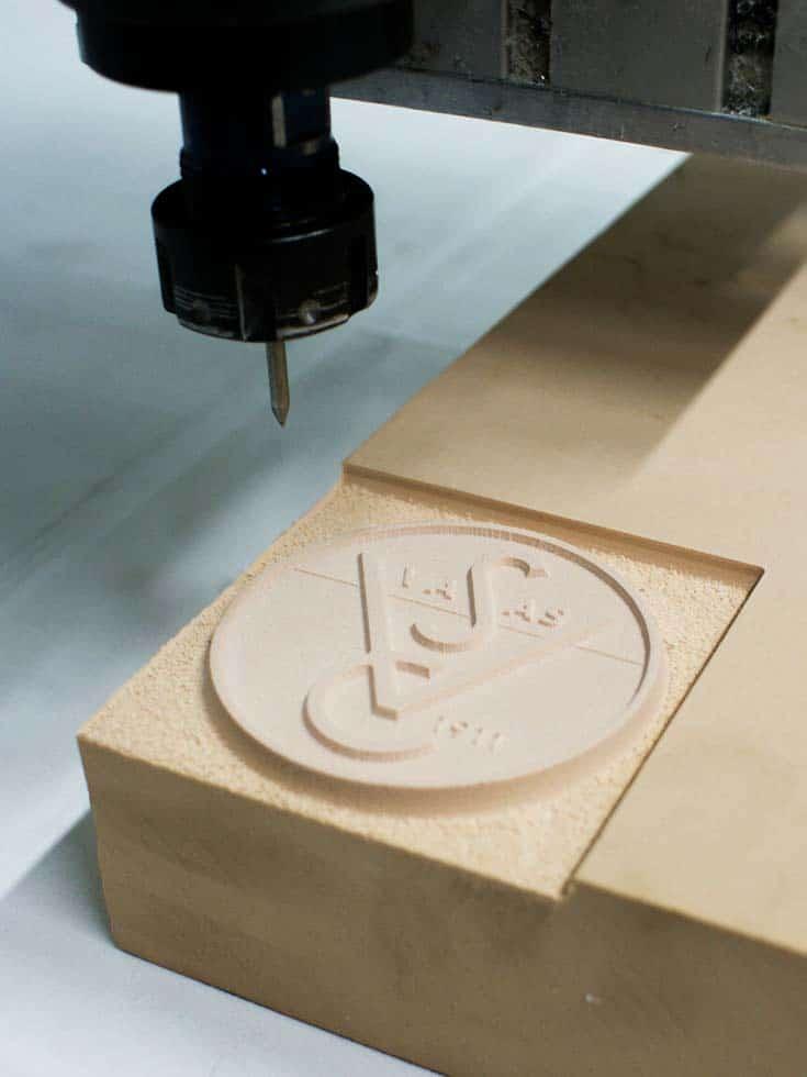 A CNC gép marófeje alatt ott a fából kimart öntőforma a Vasas jól ismert emblémájával.