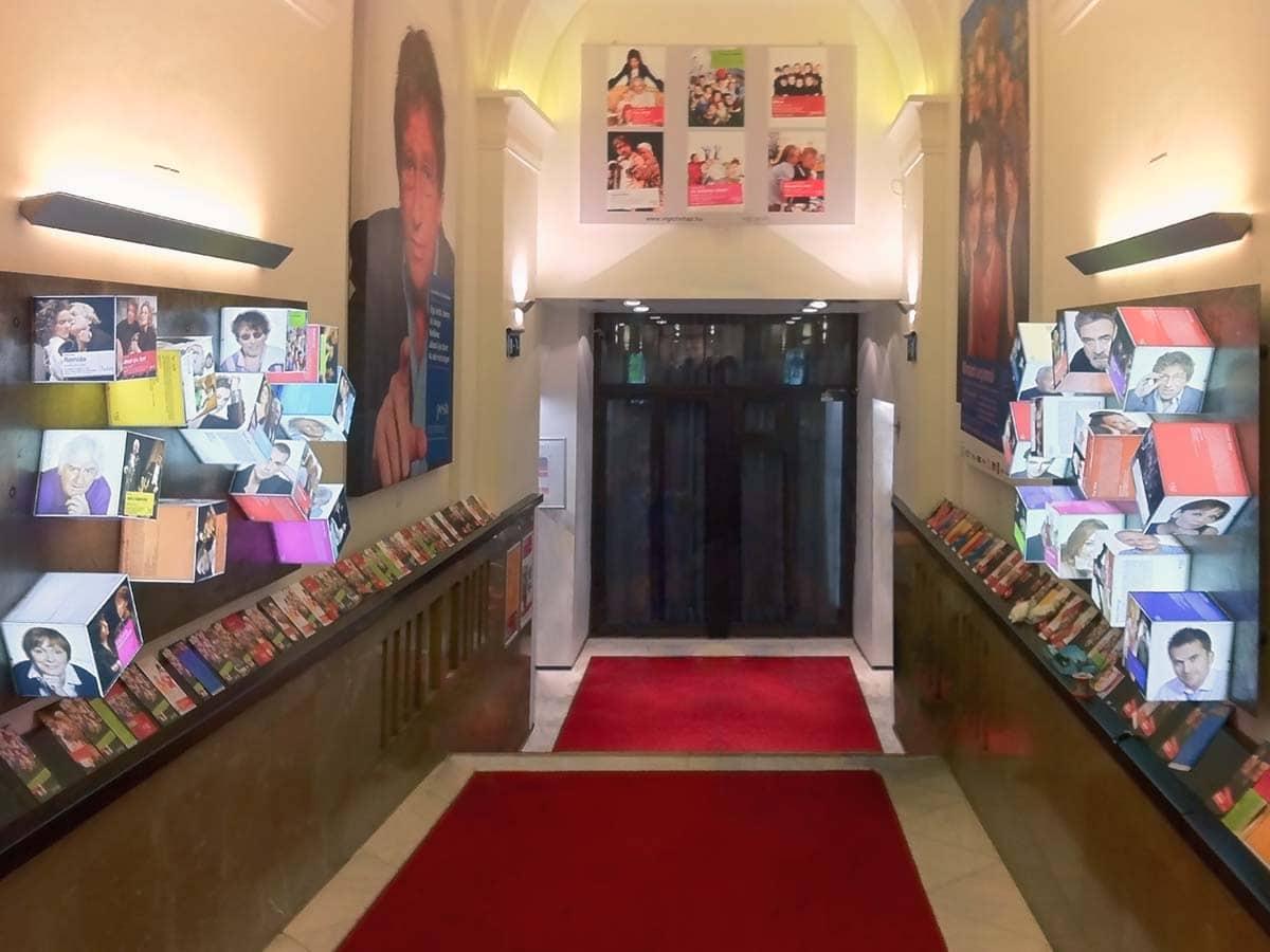 A folyosó két oldalán végigfutó fémlemezekhez világító plexikockákat rögzítettünk mágnesek segítségével, amiken a színházban játszó színészek portréi és róluk szóló szövegek jelennek meg.