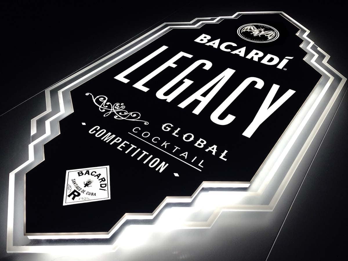 """Látványos, geometrizáló, élvilágító fali display a """"Bacardi LEGACY Global Cocktail Competition"""" felirattal és a márka logójával. Elegáns fehér fénnyel ragyog a sötét háttér előtt."""