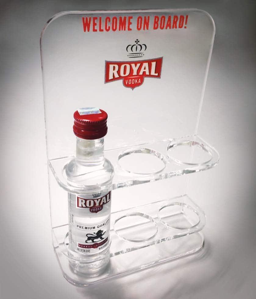 """Átlátszó Royal Vodka asztali display három darab kisméretű üveg stílusos tárolására. Rajta vörös """"Welcome on Board!"""" felirattal."""