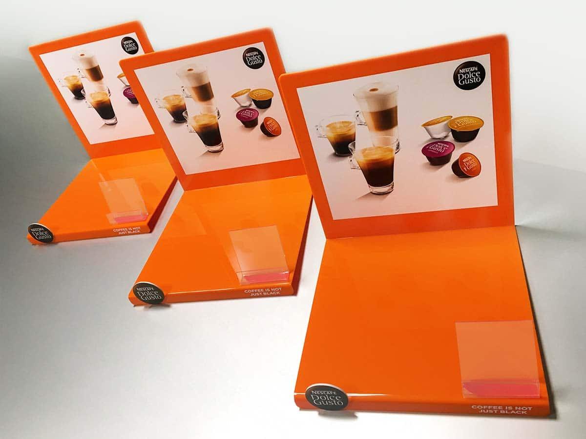 Narancsszínű nyomtatott és hajlított asztali displayek.