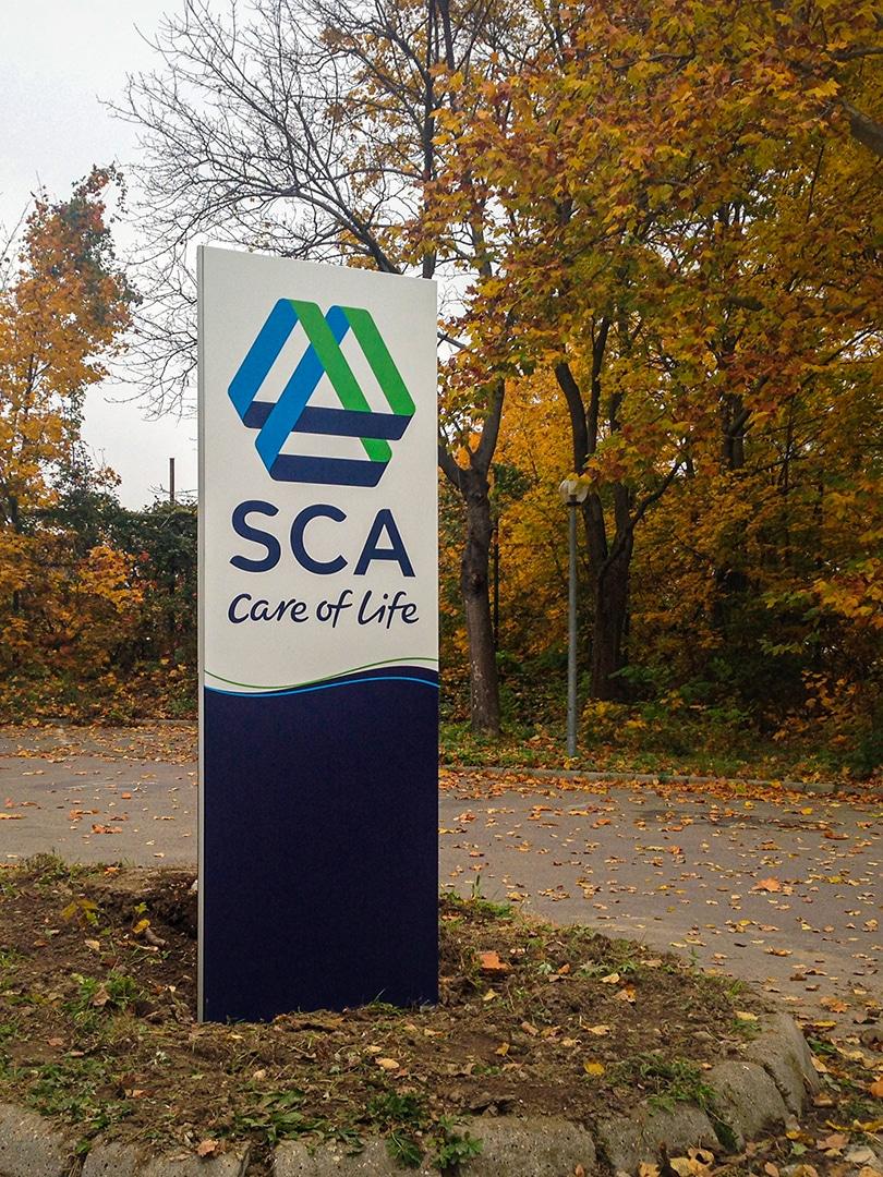 Logóval és az SCA arculati színeivel ellátott totemoszlop az irodához vezető út közepén álló járdaszigeten.