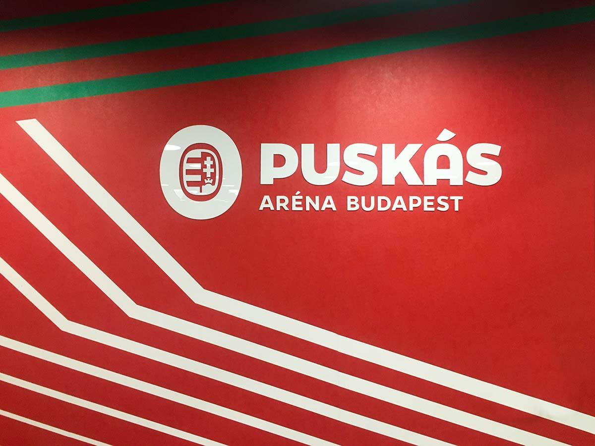 Vörös falfelületen zöld és fehér sávok futnak, köztük a Puskás Aréna nagyméretű fehér plexilogójával.