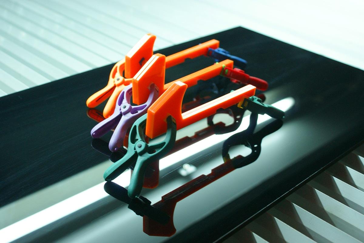 Három darab narancsszínű orvosi eszköz,amiket színes orvosi csipeszek tartanak egy tükröződő fekete felület felett.