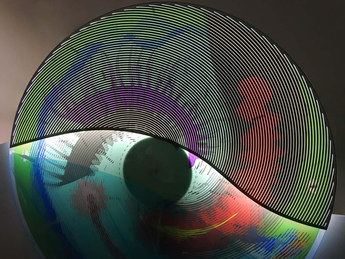 Színes, világító forgó tárcsa, amia barázdásan áttört felületen keresztül nézve mozgókép illúzióját kelti.
