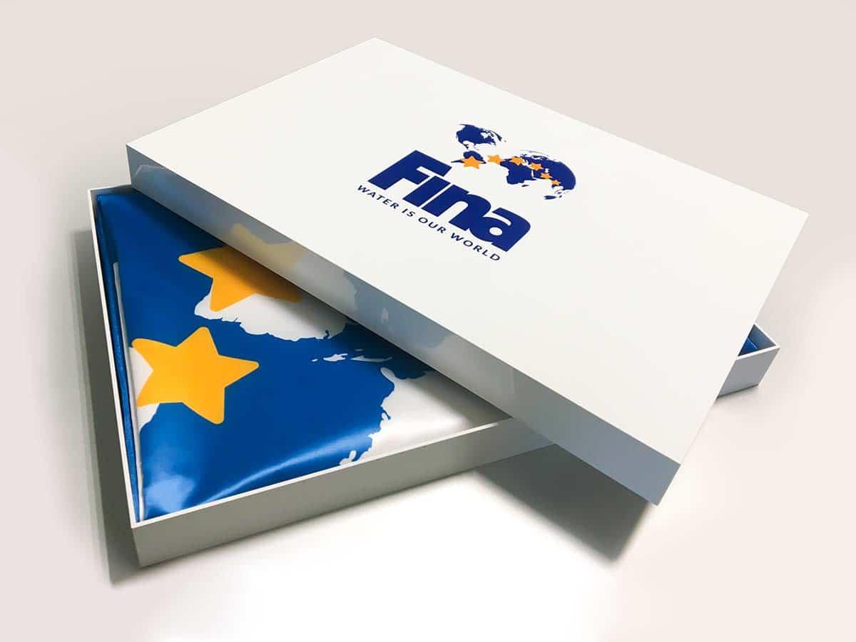 Egyszerűségében elegáns fényes fehér doboz, rajta a Fina nagyméretű logójával pompás tartó a benne lévő zászló számára.