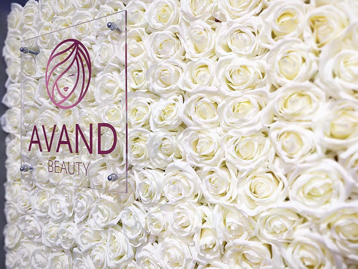 Különleges beltéri dekoráció az Avand Beauty számára. Egy egész fal fehér rózsákból, előttük pedig a cég lilás rozészínű logója átlátszó plexifelületen.