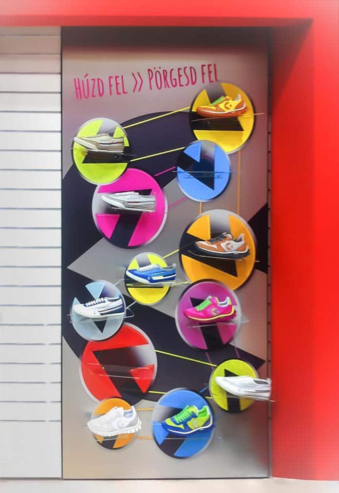 Látványos fali display, amin színes, kör alakú, forgó tartókon láthatóak a cég által forgalmazott sportcipők.