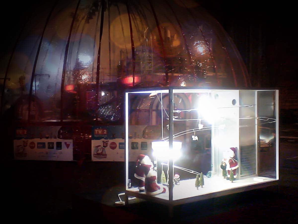 Kültéri interaktív játék ragyogó fényekkel az éjszakában egy fóliasátor előtt. Az üvegvitrinszerű játékban havas táj és mikulásfigurák kaptak helyet egy drótpálya alatt.
