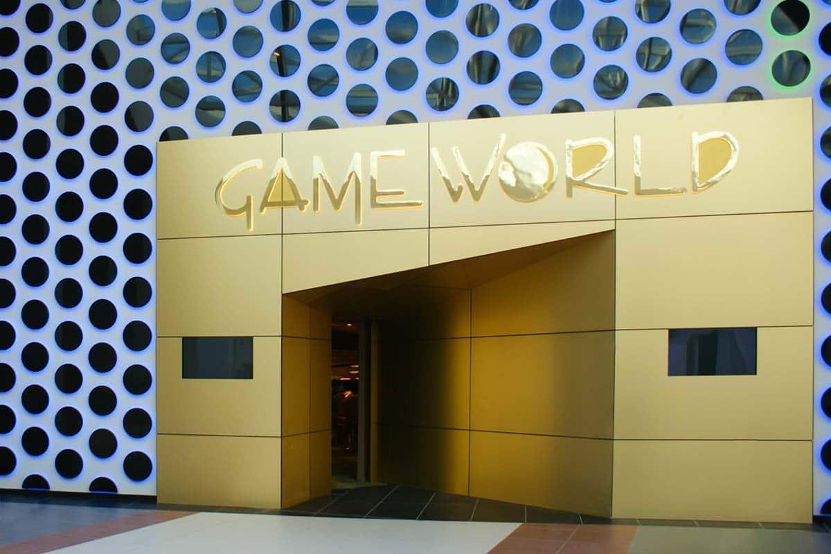 A képen a Game World portál látszik. A bejáratot arany színű lemezek veszik körül, amik modern módon, ferde metszéssel mélyednek be az ajtó irányába. A homlokzaton a nagyméretű fényes arany színű Game World logó látszik, a szögletes portál körül pedig a speciális viláítással ellátott falburkolat látszik, ahogy halvány, kékes fényben dereng.