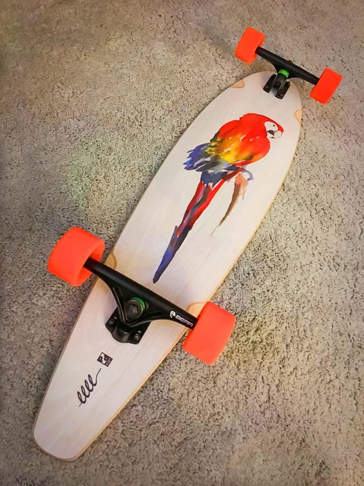 Natúr színű gördeszka, aminek az aljára egy aquarell technikát imitáló vörös ara papagáj képe van nyomtatva.