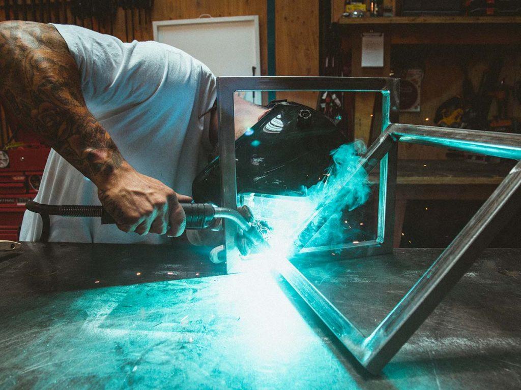 Egy fiatalember hegesztőmaszkban dolgozik azon, hogy két fémkeretet összehegesszen.
