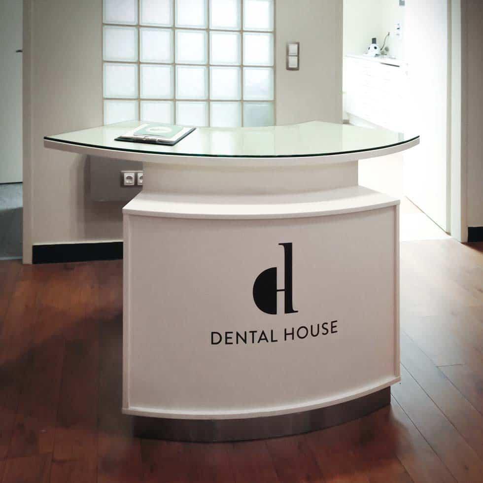 Fehér, íves kialakítású elegáns recepciós pult a Dental House fekete logójával a frontoldalon. Mögötte üvegtéglákból kirakott felülettel, fehér falakkal és egy nyitott ajtóval, amin keresztül látszik a fényes rendelő.