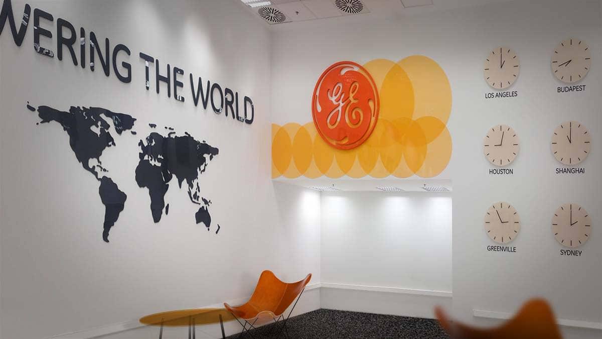 """A General Electric 7-es épületének fogadótere nagyméretű """"Powering the world"""" felirattal és világtérképpel, látványos narancsszínű GE logóval, mögötte egyedi sárga faldekorációval és világórákkal a falon."""