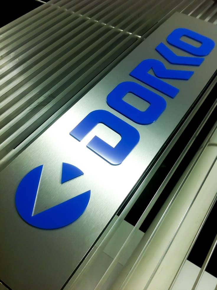 Egyedi, kék színű Dorko logó fémlemezre applikálva. Még a vágógépen van megörökítve közvetlenül az elkészülése után.