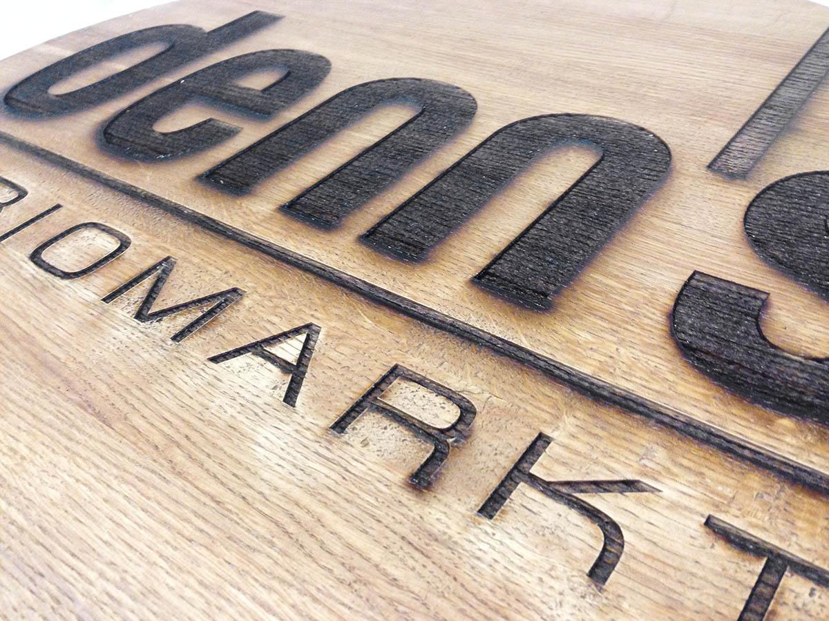 Közelkép a rusztikus falemezbe lézerrel gravírozott Denn's logóról.