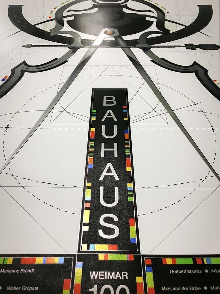 """Fényes plexitábla, amin fehér alapon szerkesztési rajz, egy diszes körzőmotívum, más ornamentikák és fekete alapon egy nagyméretű """"Bauhaus"""" felirat látszik."""