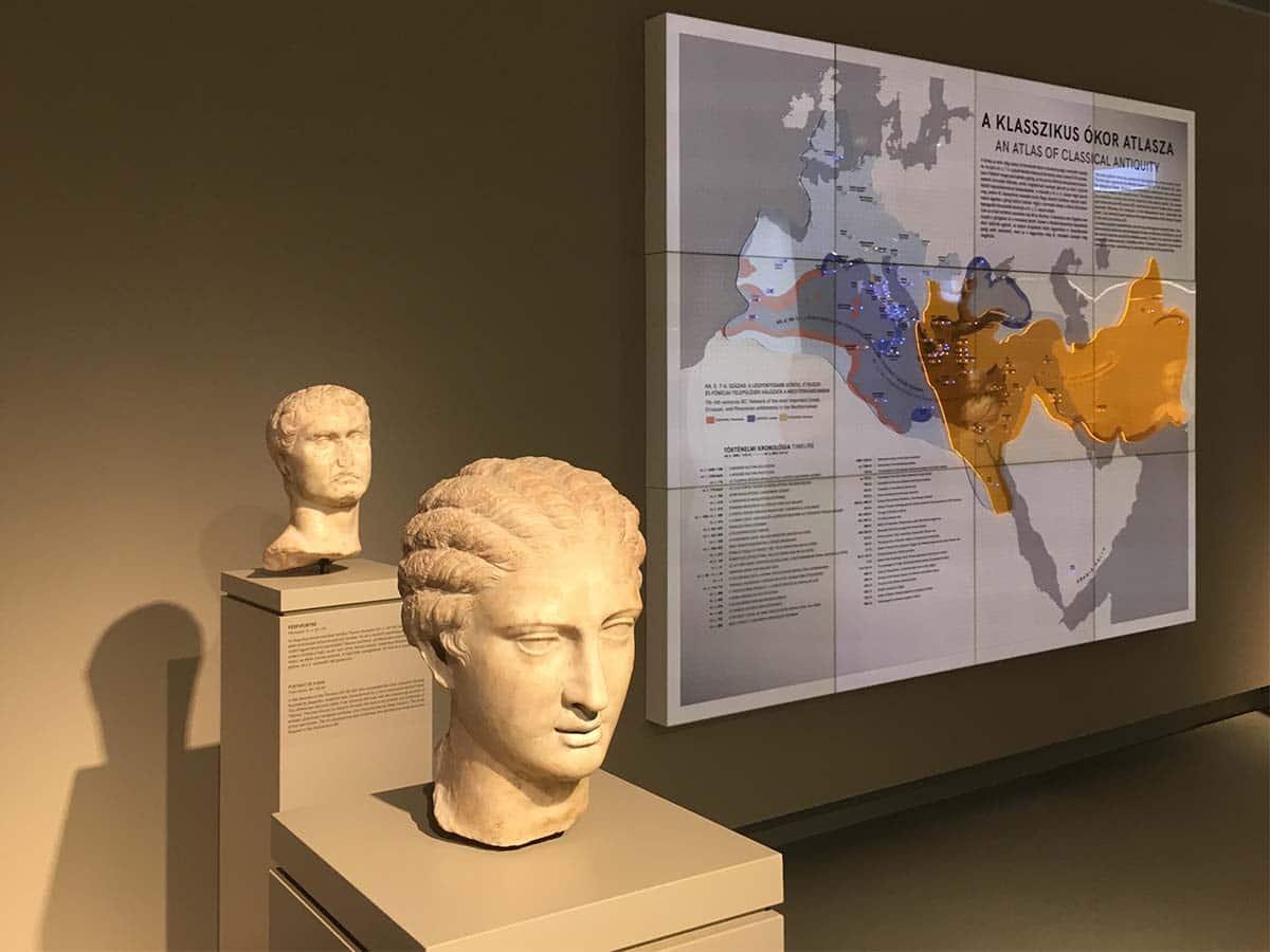 A Szépművészeti Múzeum ókor kiállítása korabeli antik szoborportékkal az előtérben és látványos plexitérképpel a háttérben.