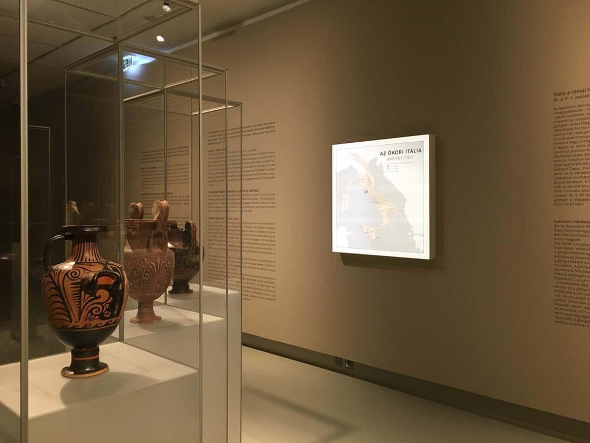 A Szépművészeti Múzeum ókor kiállítása antik vázákkal és edényekkel az előtérben lévő vitrinekben és világító plexitérképpel valamint vágott falfeliratokkal a háttérben.