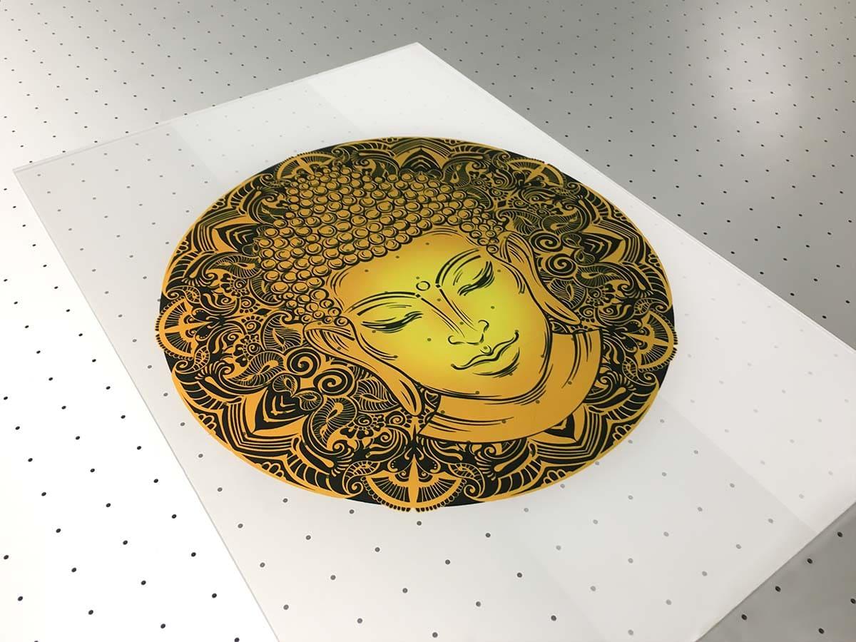 Nagyméretű üvegtáblára készült sárga alapon fekete ornamentális Buddhaportré.