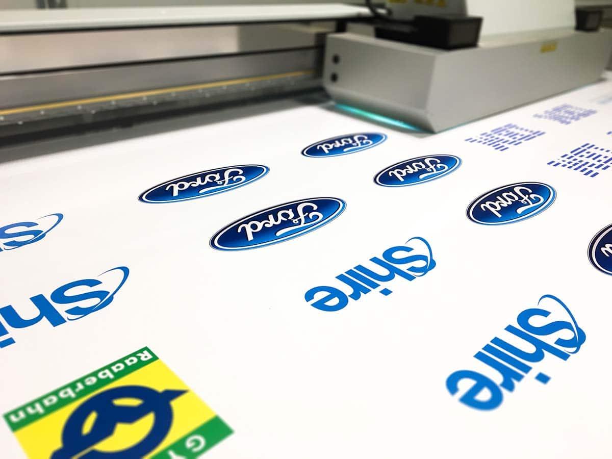 Ipari UV nyomtató dolgozik rajta, hogy a Duna Tower partnereinek logóit (IBM, Ford, Shire stb.) rányomtassa a plexitáblára, amiből ezeket később kivágva elkészülnek a különböző jelzőtáblák az irodaház parkolójába.