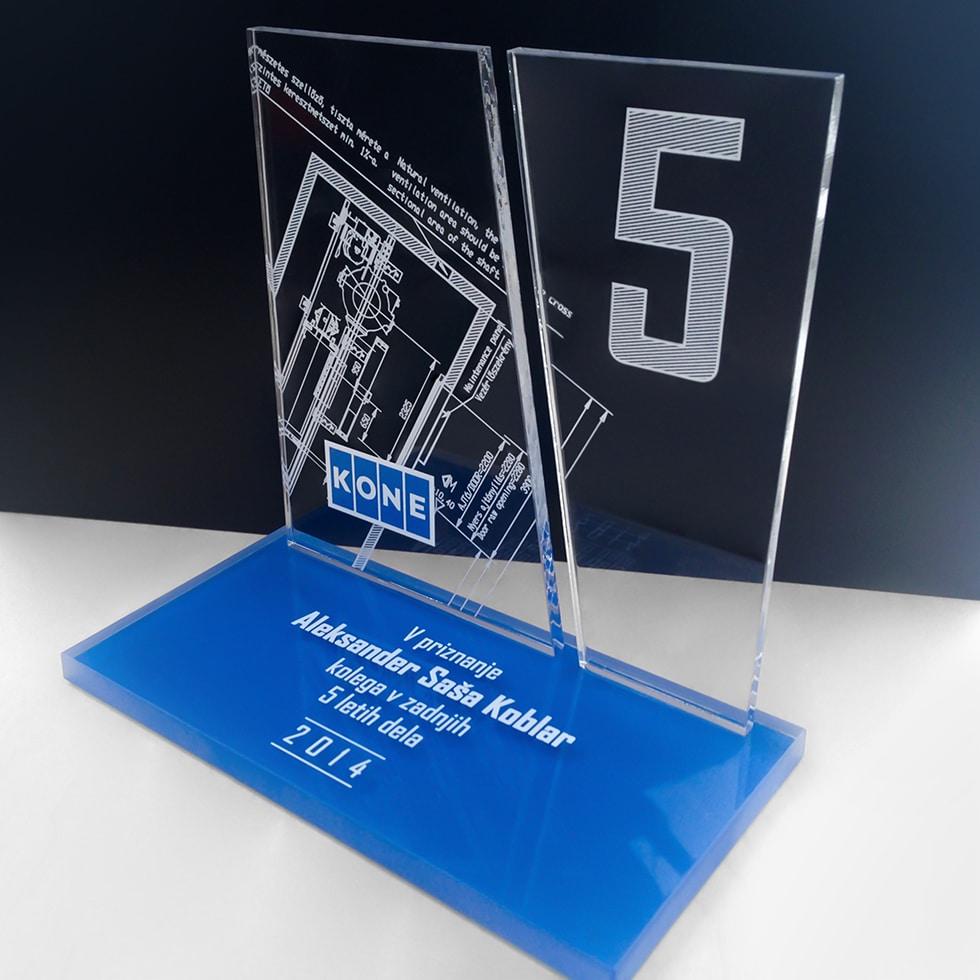 Lézergravírozott két részből összeálló átlátszó plexi hordoza a nagyméretű számot és egy műszaki rajzot, a kékkel színezett aljú plexilap pedig a kitüntetett nevét és a további információkat.