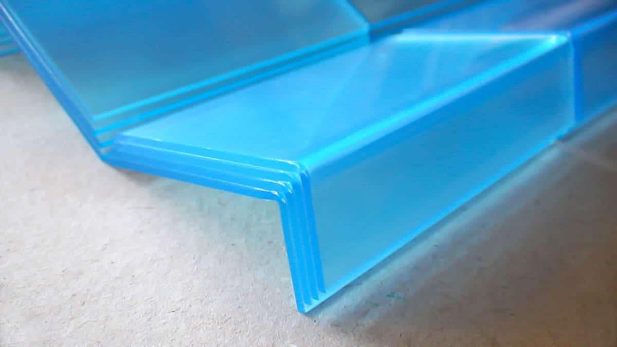 Több ponton hajlított átlátszó kék plexilapokból kialakított laptartók.