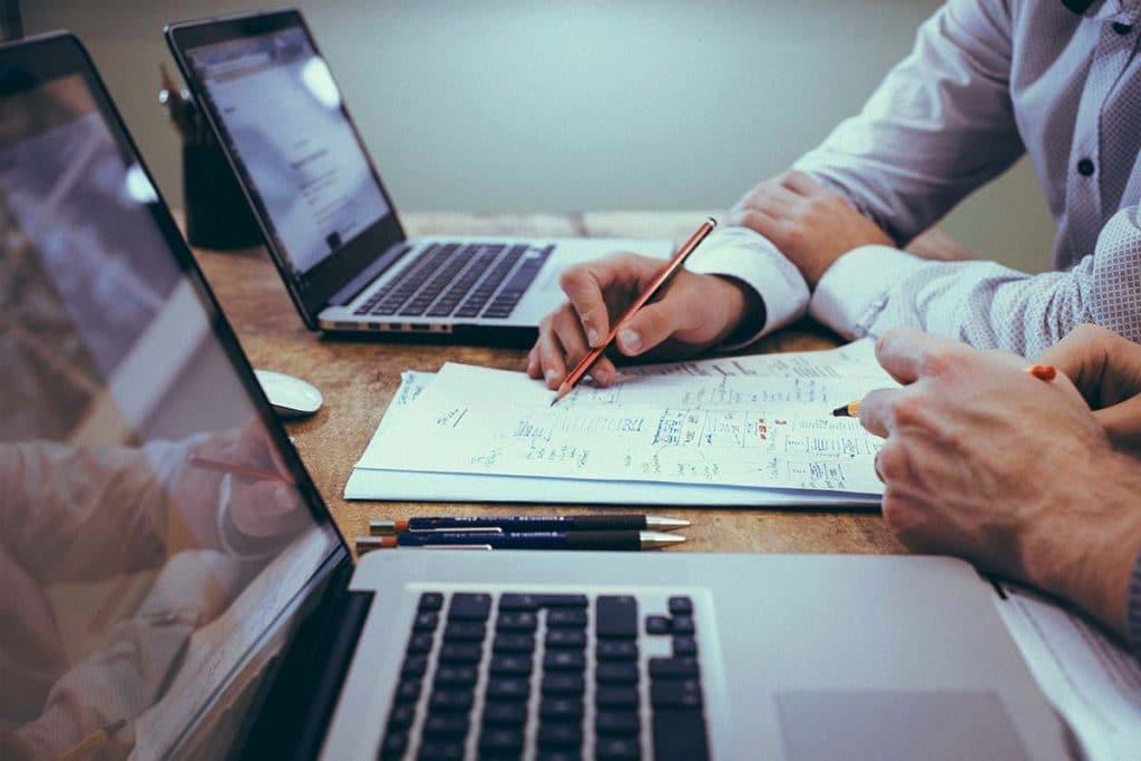 Közelkép, amin férfiak kezei látzsnak, amint laptopok mellett egy füzetre írva és rajzolva a projekt részleteit egyeztetik.