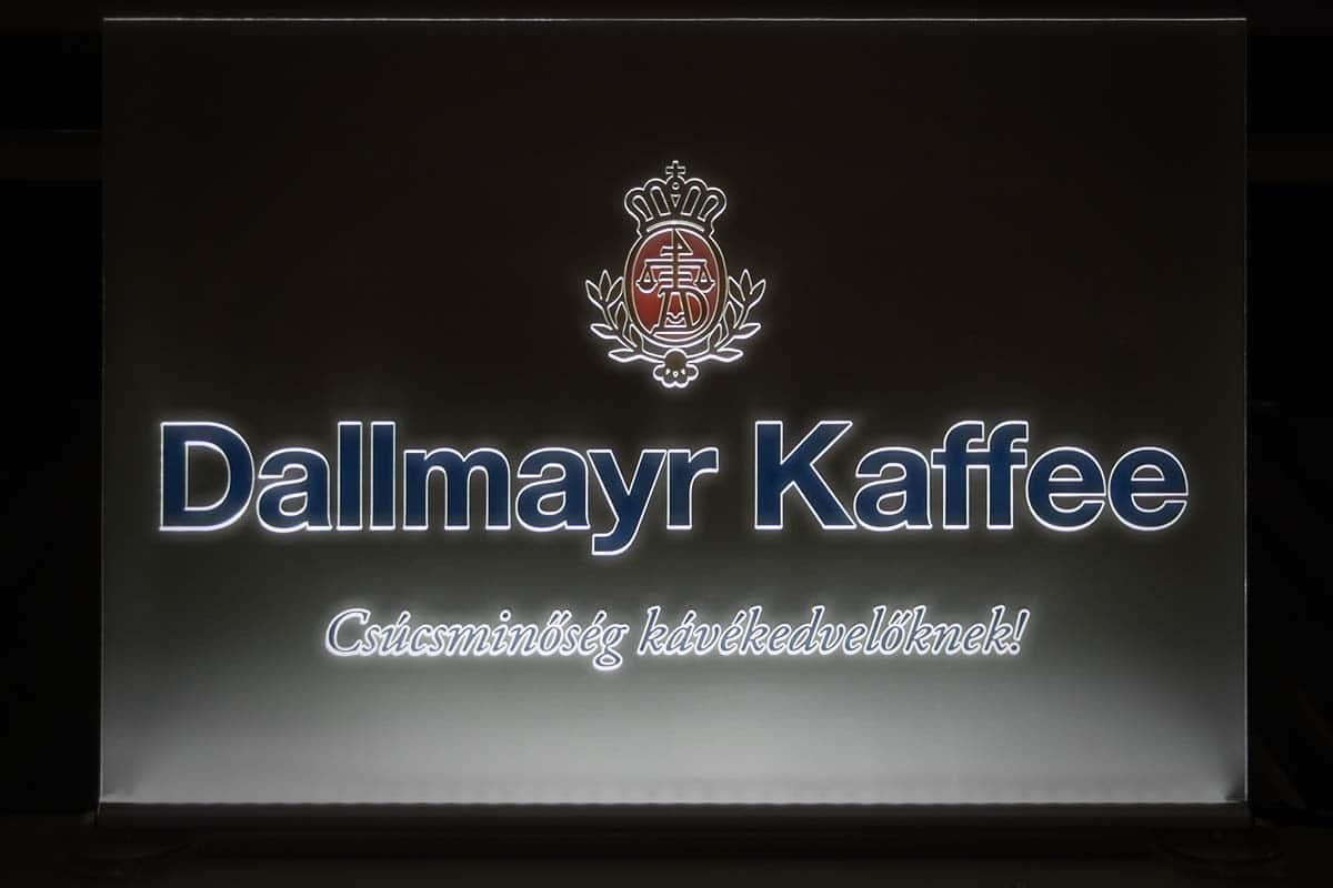 """Dallmayr Kaffee élvilágító tábla a cég logójával és a """"Csúcsminőség kávékedvelőknek!"""" szlogennel."""
