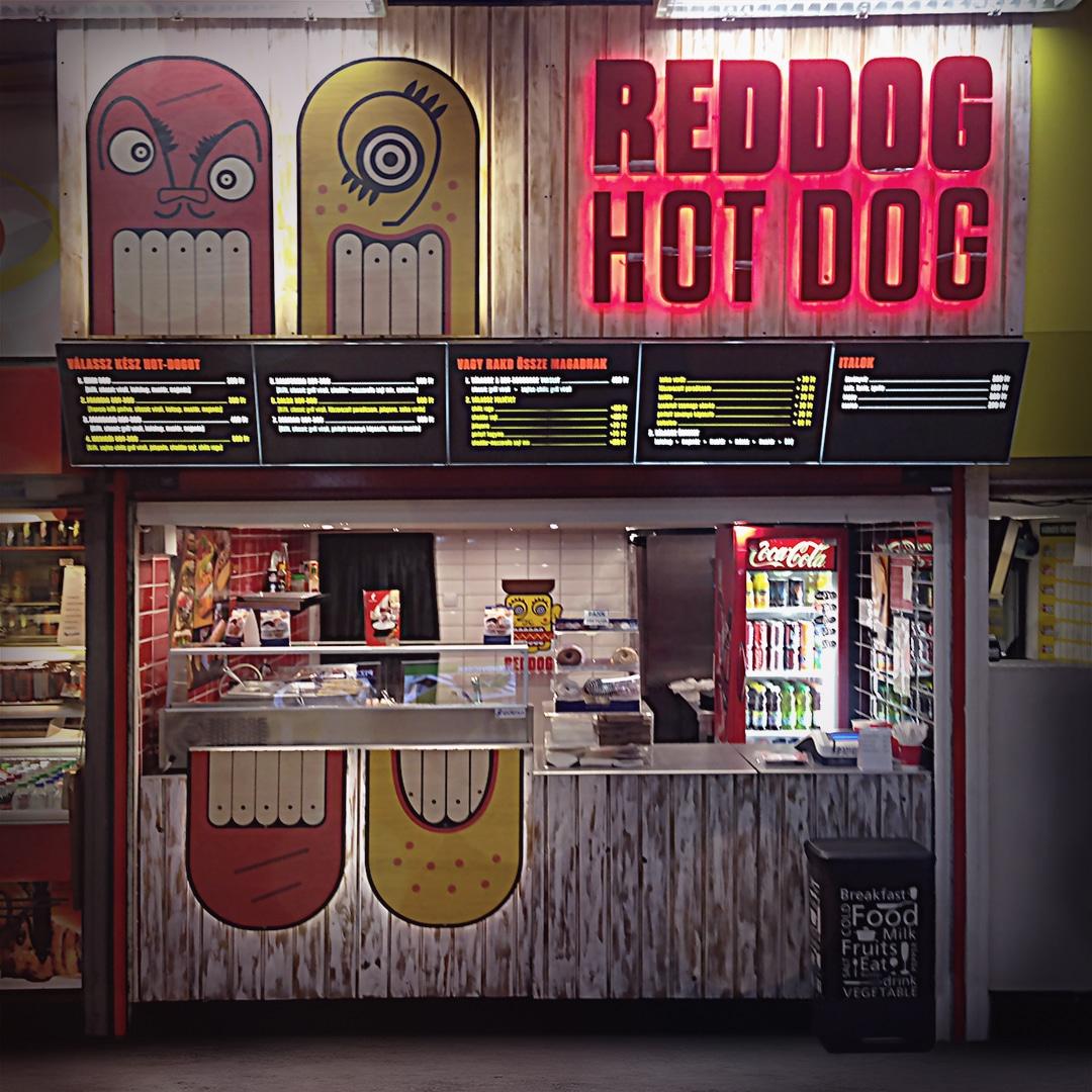 Világító RED DOG HOT DOG felirat és játékos homlokzati dekoráció, ami az extravagáns hot dog sütöde két vicsorgó kabalafiguráját ábrázolja.