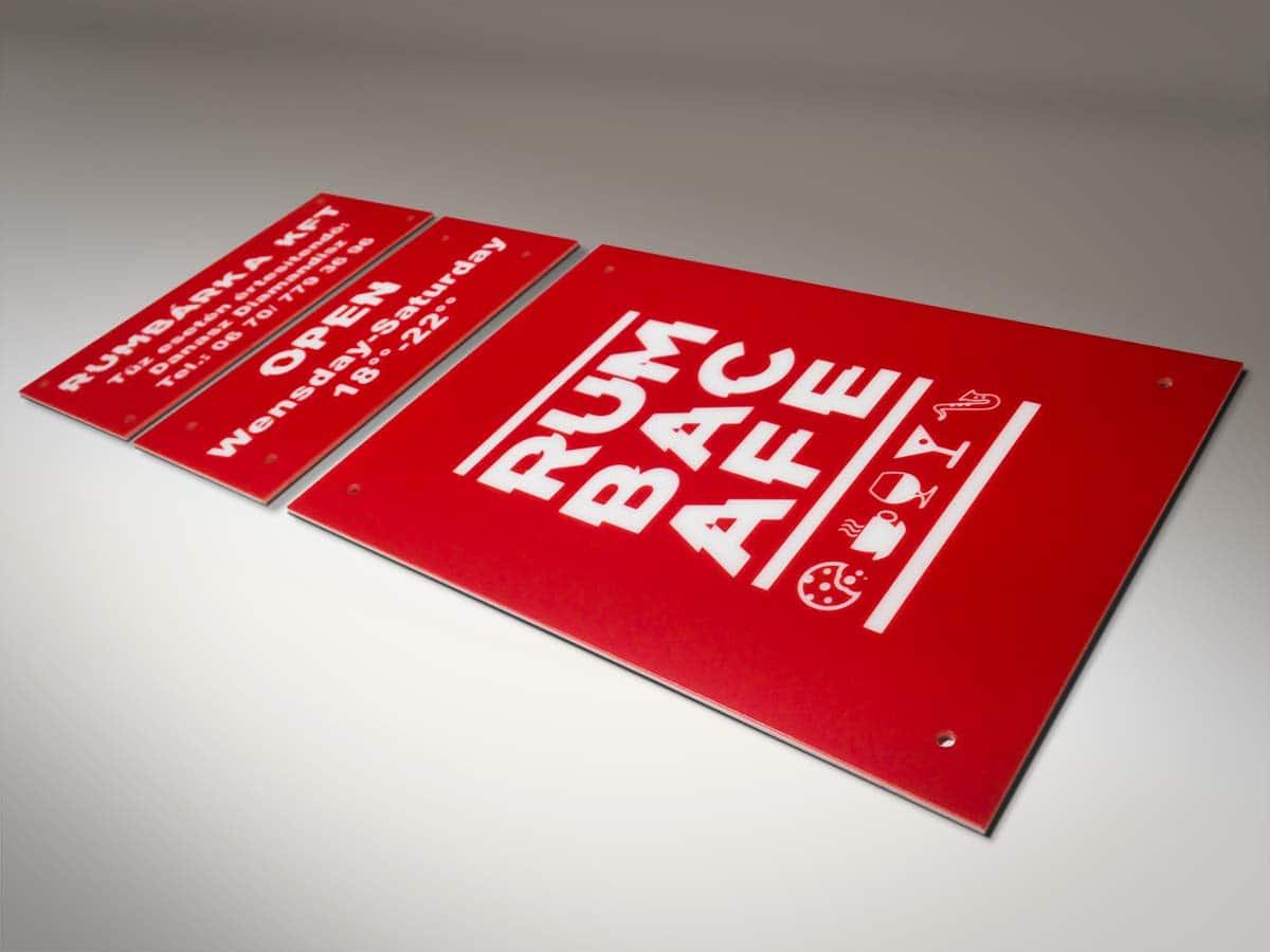 Három darab vörös plexitábla fehér feliratokkal. A legnagyobbon a Rumba Cafe logója látható, a másik kettőn pedig a nyitvatartás és általános információk olvashatóak.