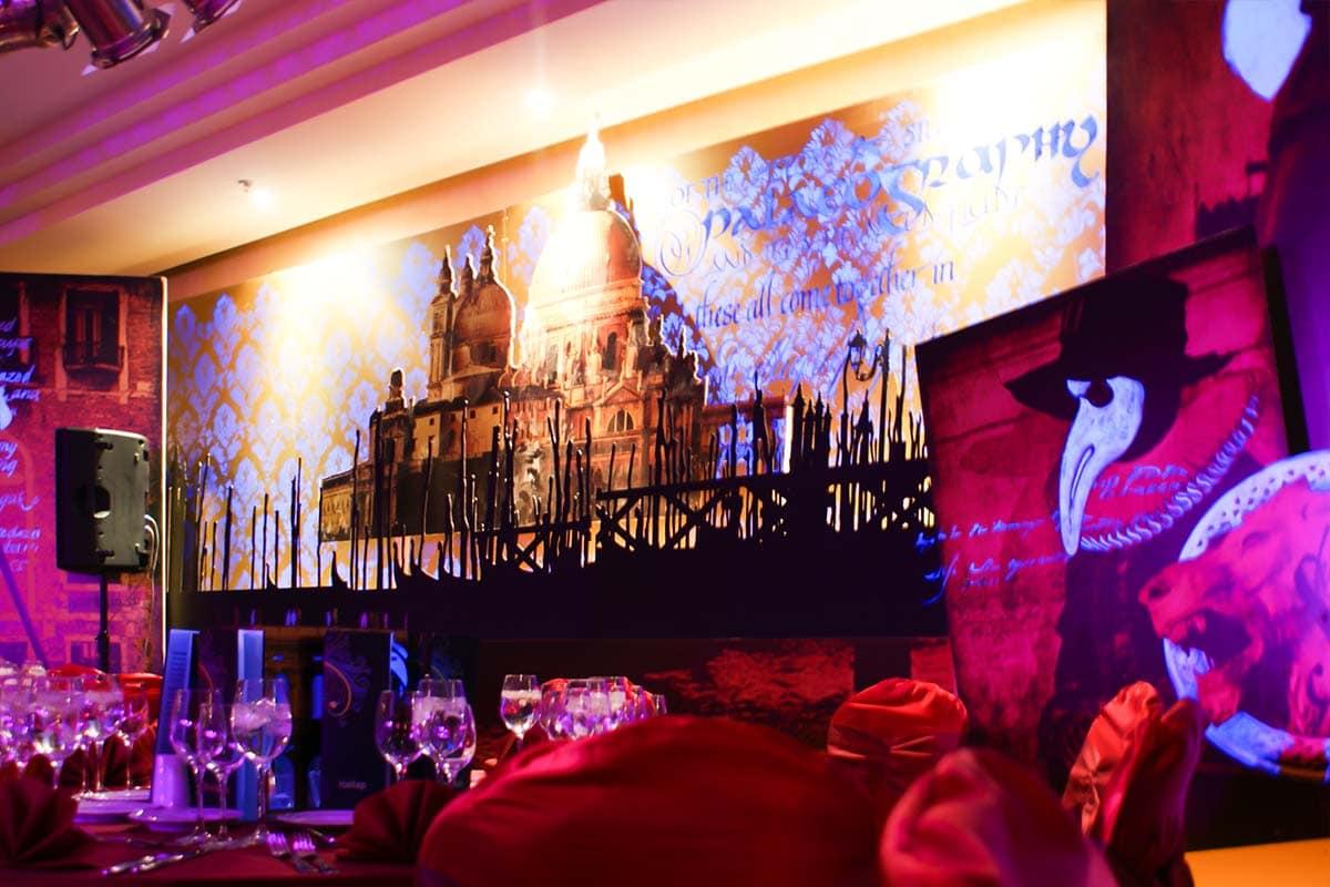 Rózsaszínes, lilás nyomtatott táblán egy velencei maszkos alak képe. Mellette kristálypohatak a fényűzően díszített asztalokon, a háttérben Velence sárgás tájképe vetített kék, barokkos sormintával.