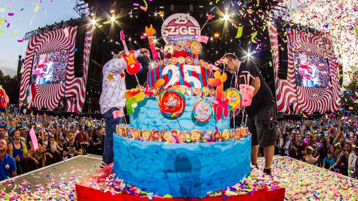 A színpompás Sziget torta ünnepélyes felvágása a nagyszínpad előtt konfettiesőben. A kék tortát a gitárt, lufikutyát, nyalókákat és vizipisztolyt idéző tortadíszek teszik még különlegesebbé.