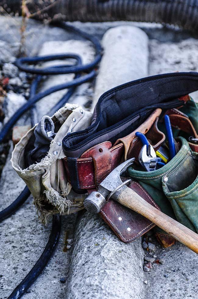 Egy munkás szerszámosöve látszik a képen egy helyszínen lévő betonelemre fektetve. Kalapács, csőkulcs és más hasznos eszközök lógnak az öv oldalán.