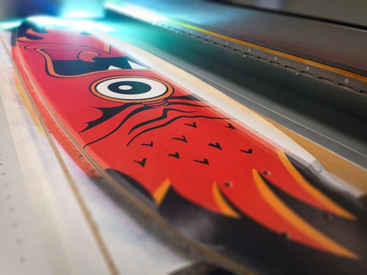 Közeli egy gőrdeszkáról, amire épp most nyomtatja rá a piros, egyszemű szörnyecskét ábrázoló mintát a világító nyomtatófej.