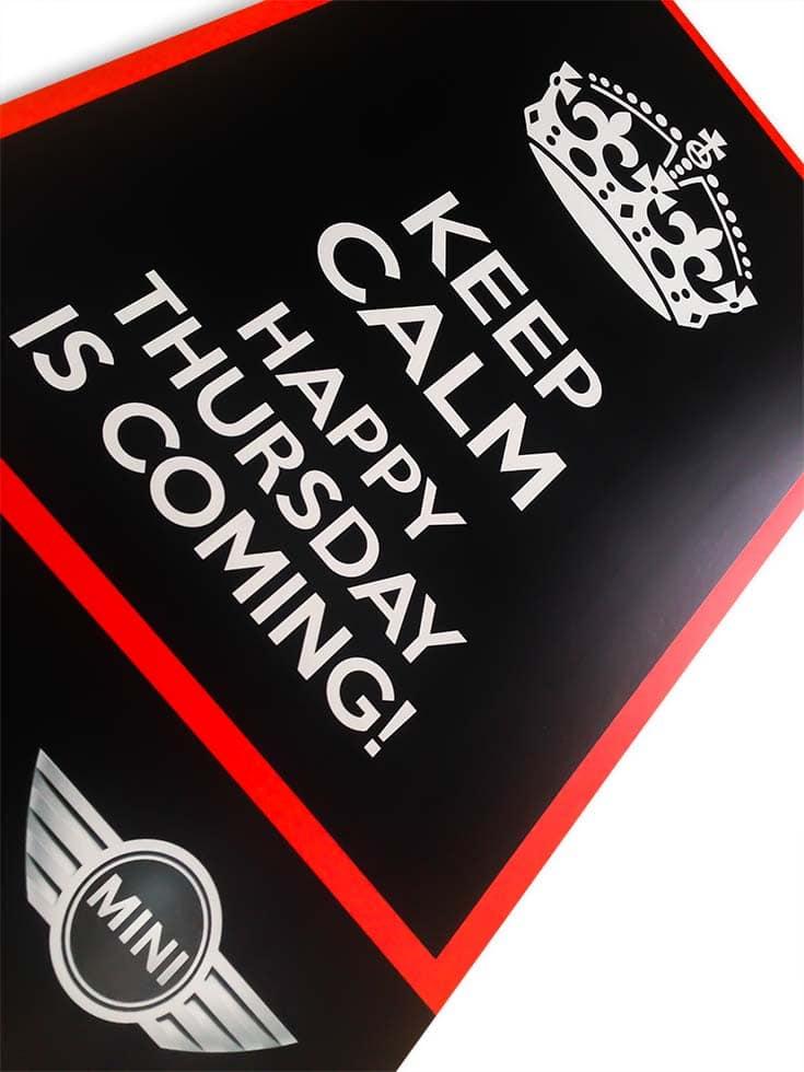 """Fekete plexitábla vörös szegéllyel és határolócsíkkal, a Mini logójával és a nagyméretű """"Keep Calm, Happy thursday is coming!"""" felirattal, ami felett egy korona szikuettje látható."""