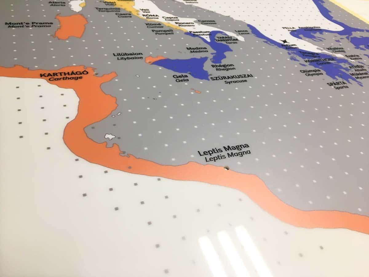 Az ókori Karthágónak és környékének szürke-kék-narancs térképe látszik egy átlátszó plexire nyomtatva.