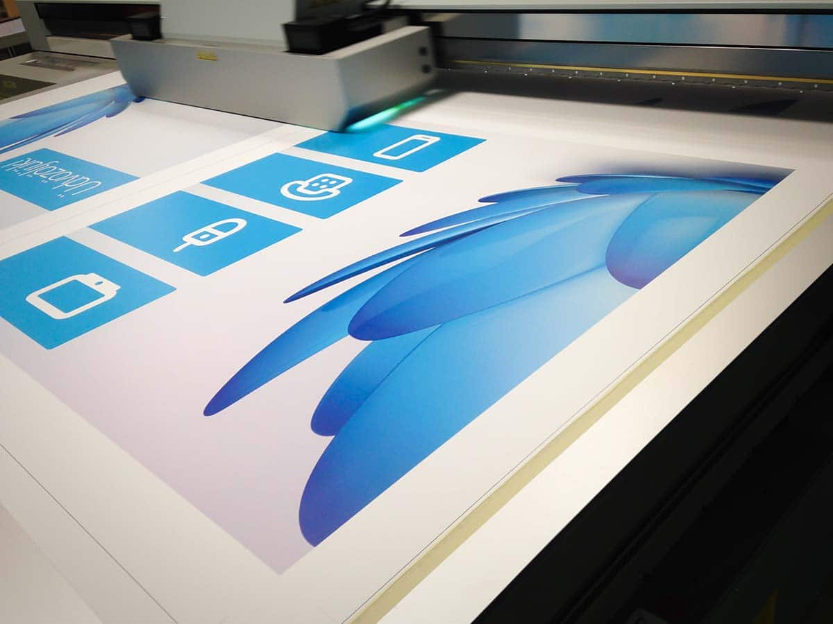 A nyomtatógép épp most fejezi be az UPC számára készülő fehér alapon kék logóval díszített üdvözlőtábláit.