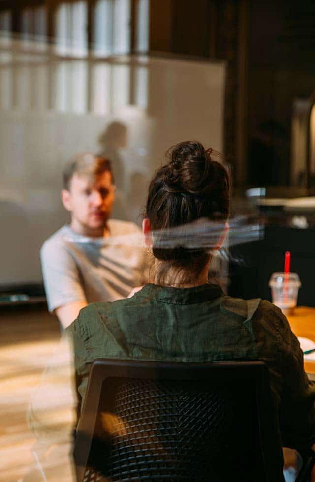 Fiatal nő tart előzetes igényfelmérést férfi ügyfelével tárgyalva egy plexifal mögött.